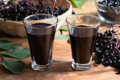 two-glasses-elderberry-syrup-wooden-background-two-glasses-elderberry-syrup-wooden-table-fresh-elderberries-99642448